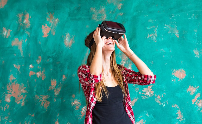 Picture of a woman next to a wall wearing a virtual reality headset.