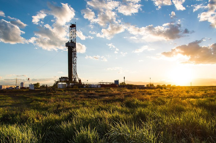 Drilling rig in a field at sunrise.