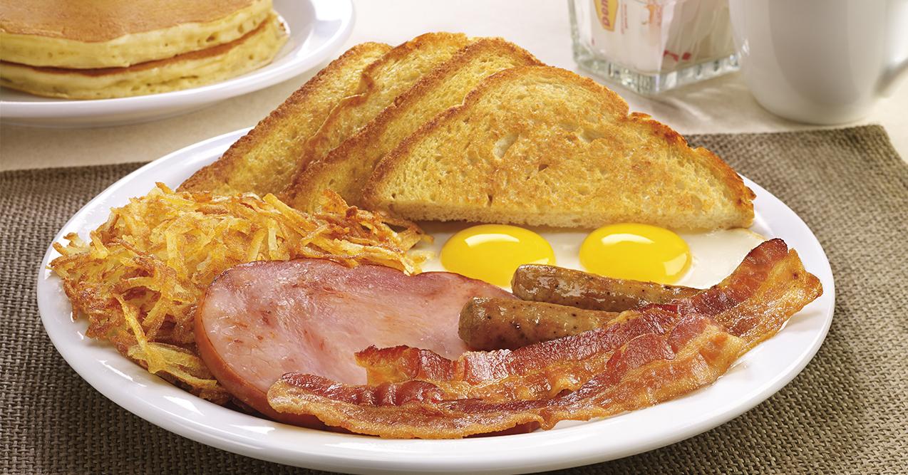 A plate of ham, sausage, bacon, eggs, potato, and bread.