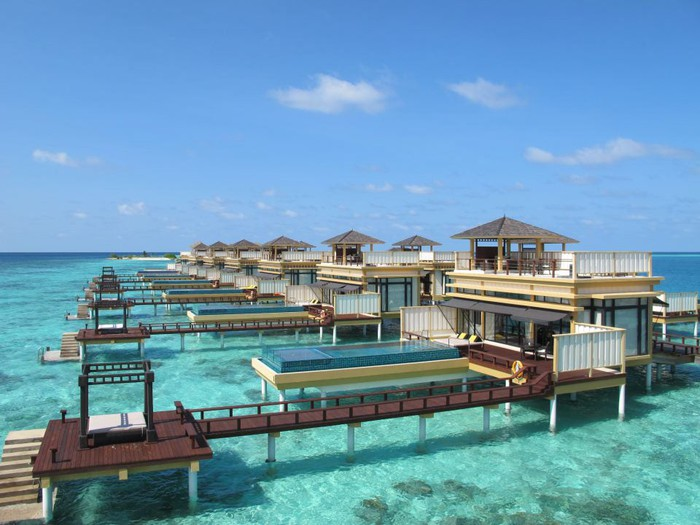 A set of bungalows on a dock over a turquoise-colored sea