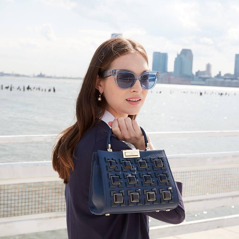 A woman holding a Kate Spade purse.