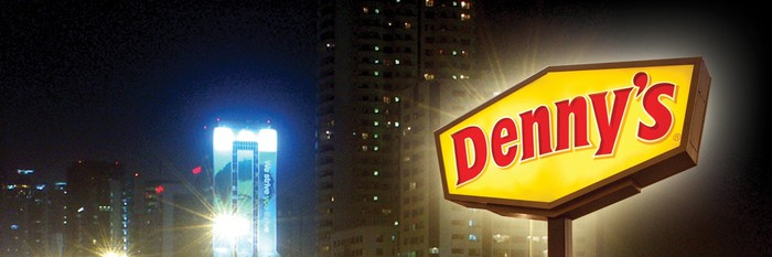 Denny's sign in front of a city landscape.