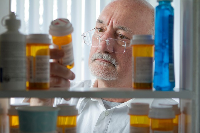 Senior citizen looks at pill bottle with his medicine cabinet open showing numerous bottles of pills.