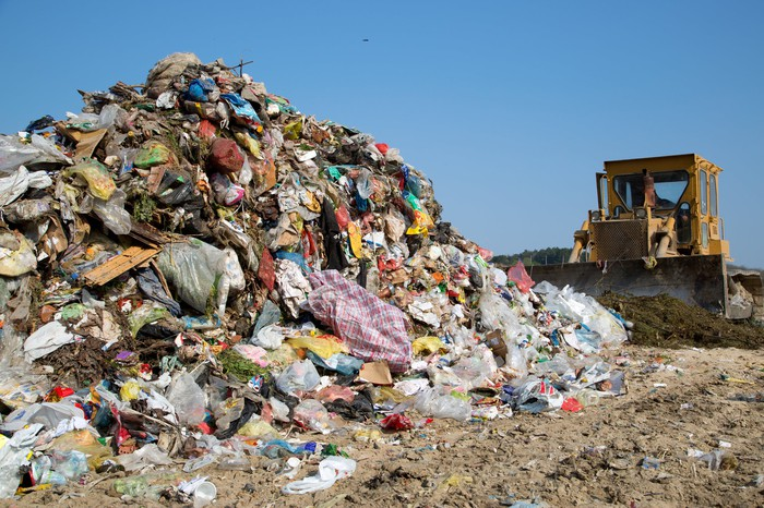 Bulldozer moving trash at a landfill.