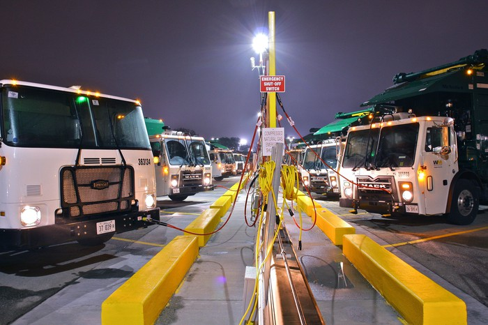 Fleet of Waste Management garbage trucks refueling.