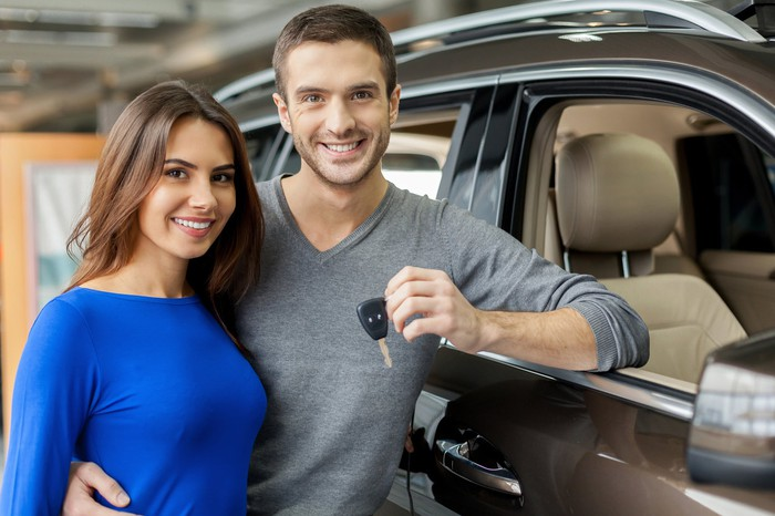 A couple holding keys to a new car
