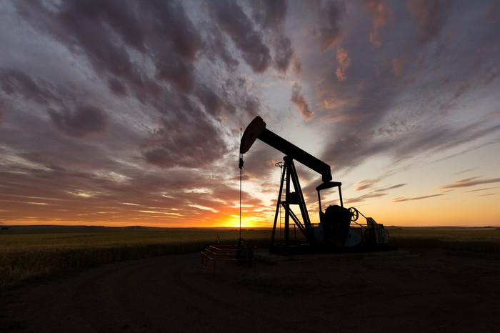 An oil pumpjack at sunrise.