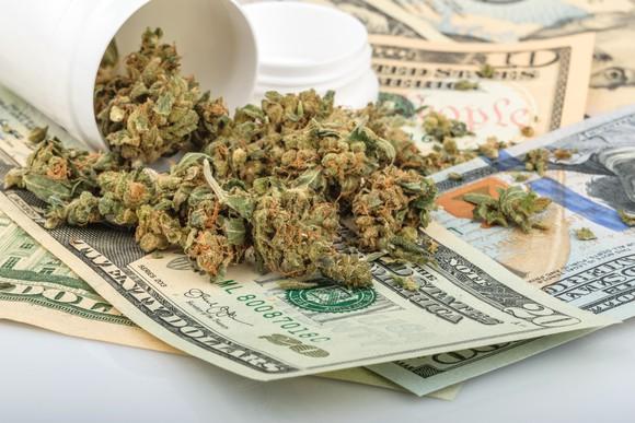 Marijuana spills out of a prescription bottle onto a pile of money.