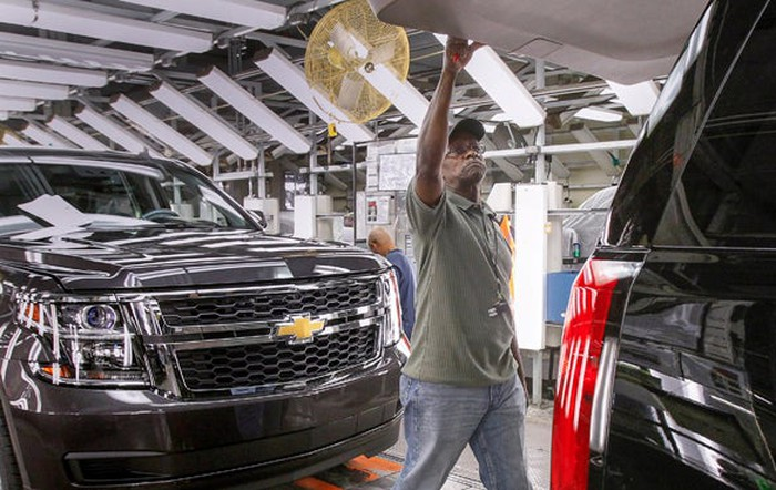 A Chevrolet SUV moving down a factory assembly line.