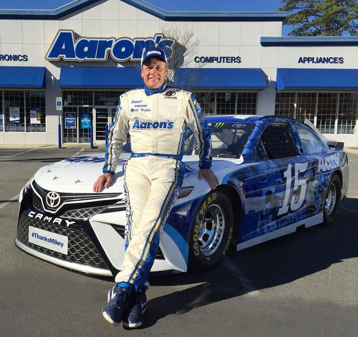 NASCAR driver Michael Waltrip standing in front of his Aaron's-sponsored car and an Aaron's store.