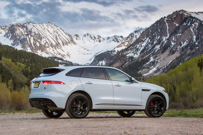 A white Jaguar F-PACE SUV with mountains in the background.