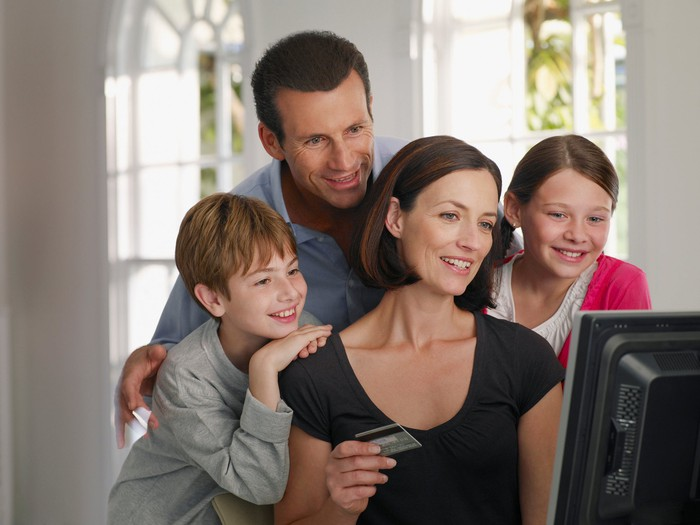A woman sits at a computer monitor with credit card in hand, while her husband, son, and daughter huddle around her, looking at the screen