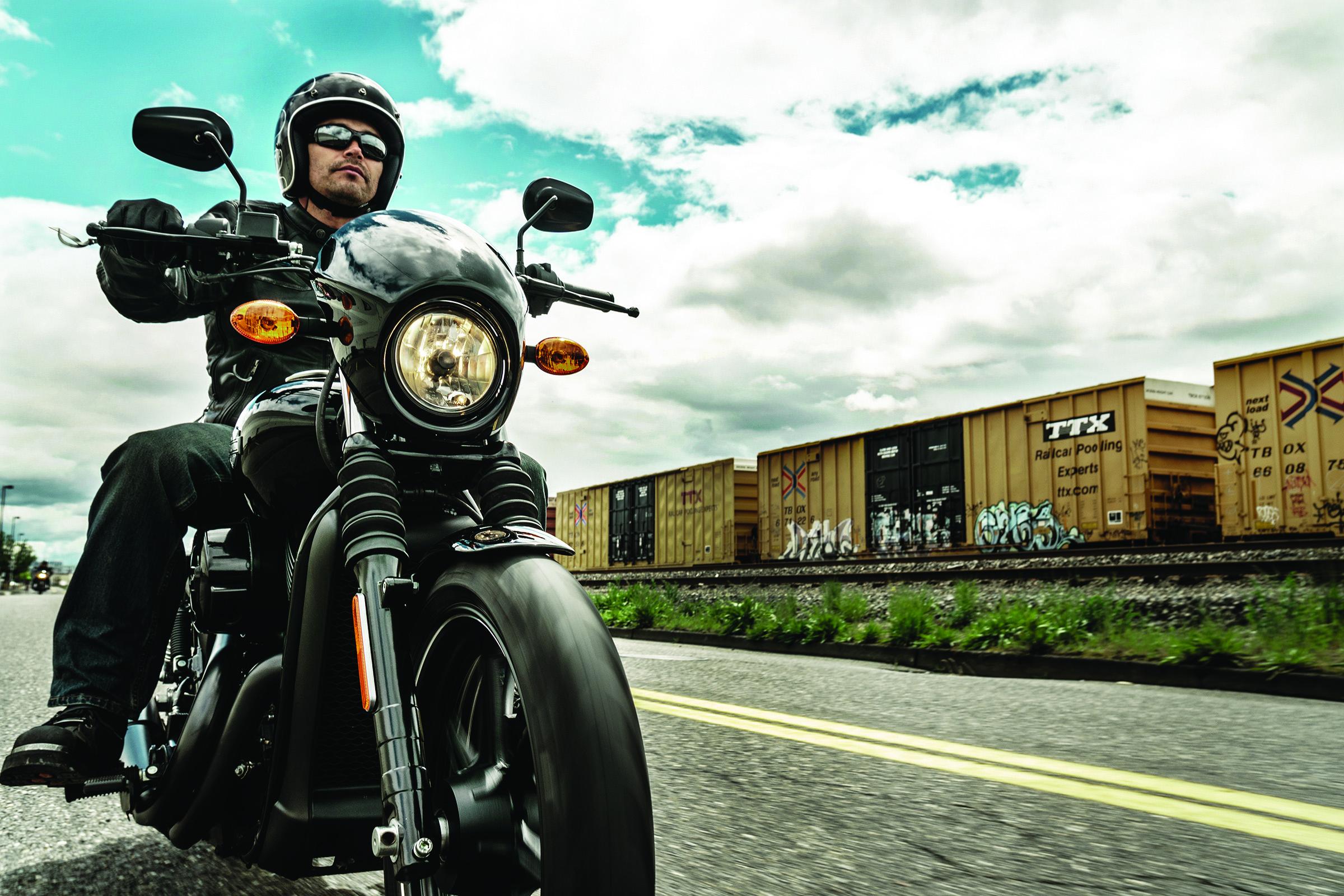 Man riding a Harley-Davidson motorcycle on street