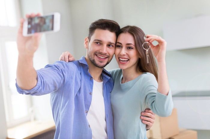 Young couple with keys to their first home.