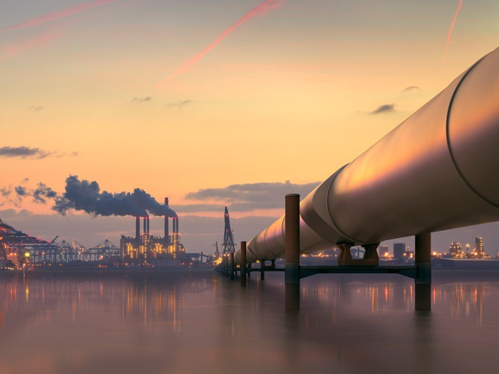 Oil pipeline in industrial district with factories at dusk.