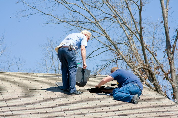 Workers repairing a house's roof