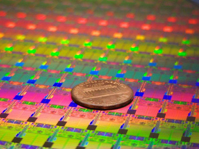 A wafer of silicon chips with a penny on top of it to show that chips are very small.