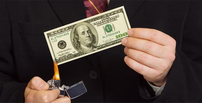 A man burning a hundred dollar bill.