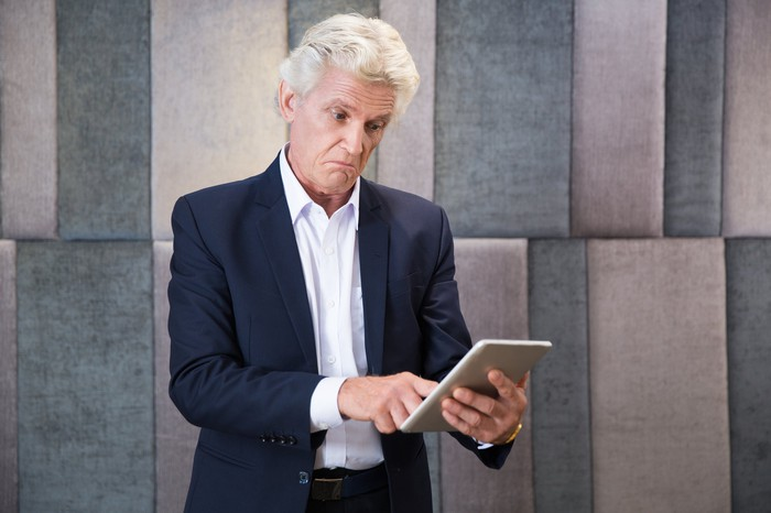 Older male looking surprised at a tablet.