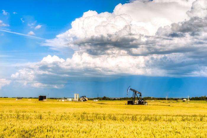 a rural landscape of Alberta, Canada, featuring a pumpjack in a field.