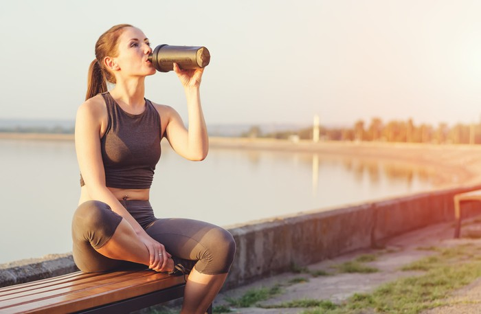 A women drinks a protein shake during a run.