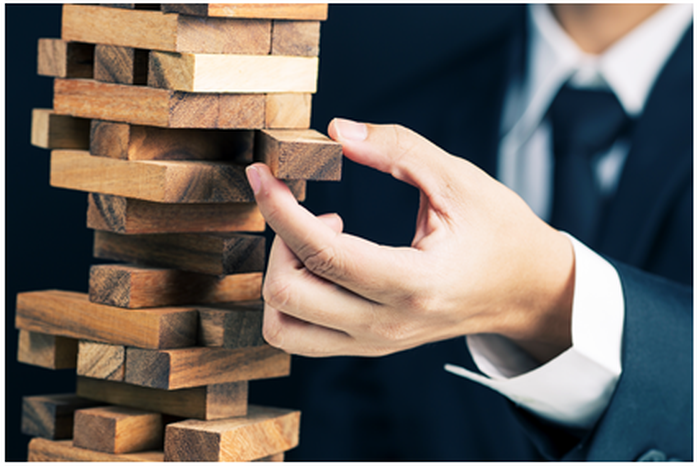 A man in a business suit playing Jinga.