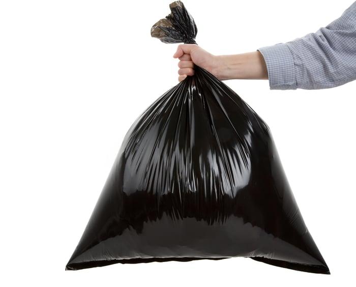 Hand holding black trash bag.
