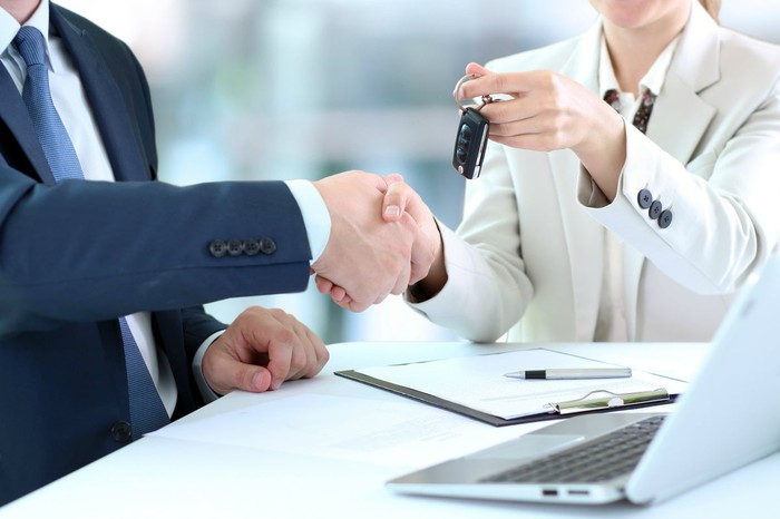 A car buyer is handed her keys.