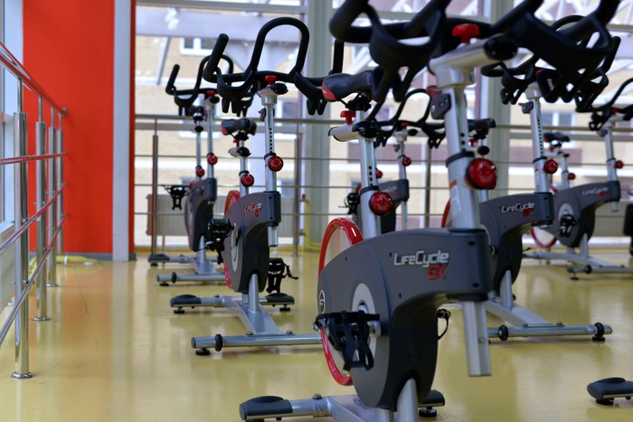 A row of stationary bikes in a gym.