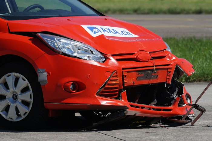 A red car with a crushed front.
