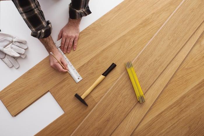 Installer laying wood flooring.