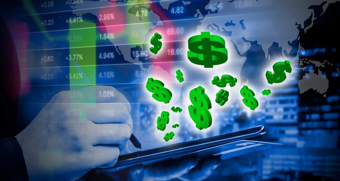 Green dollar signs flying out of computer, with stock listings and a world map in the background