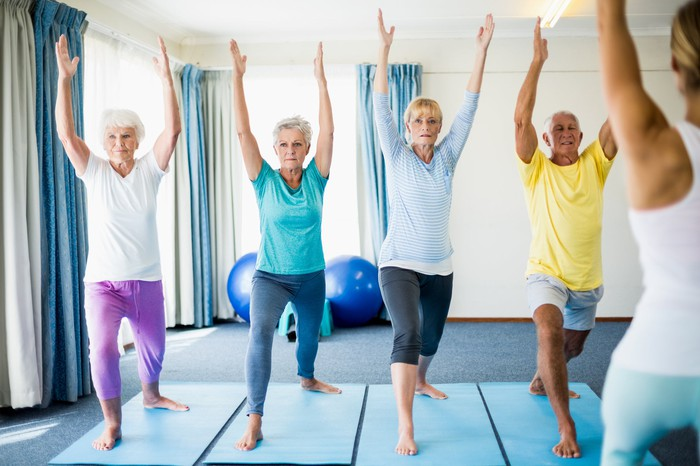 Four older people in a yoga class