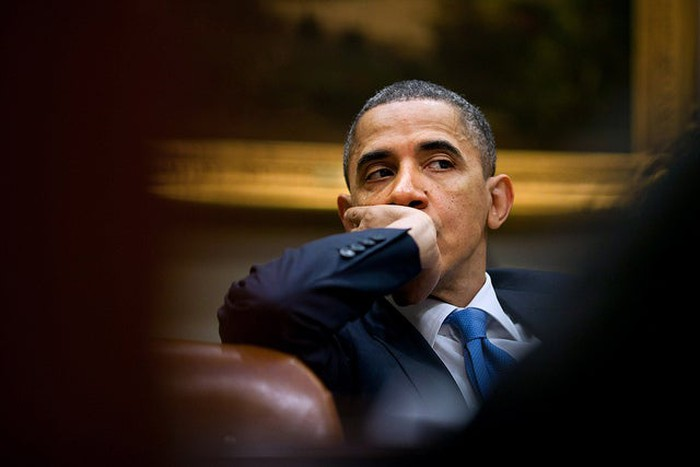 Now-former President Obama listening at a meeting with his staff.
