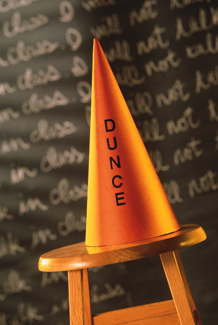 Dunce cap on a stool in front of a blackboard