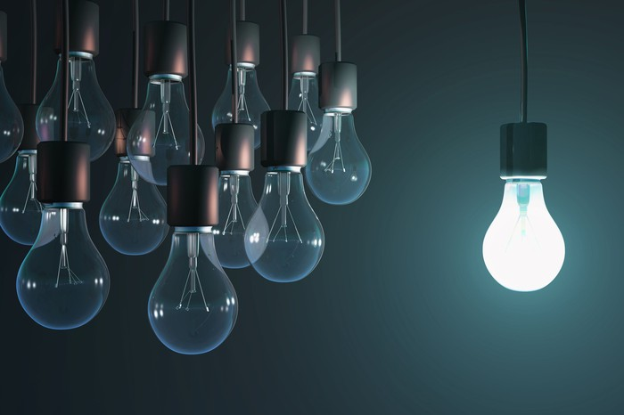 Brightly shining light bulb near cluster of unlit light bulbs.