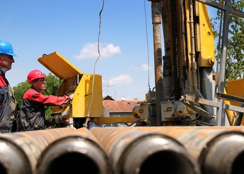 Oil field services workers with pipes and drilling rig