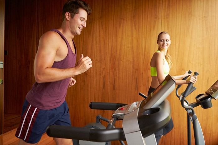 Two people working out on treadmills at home.