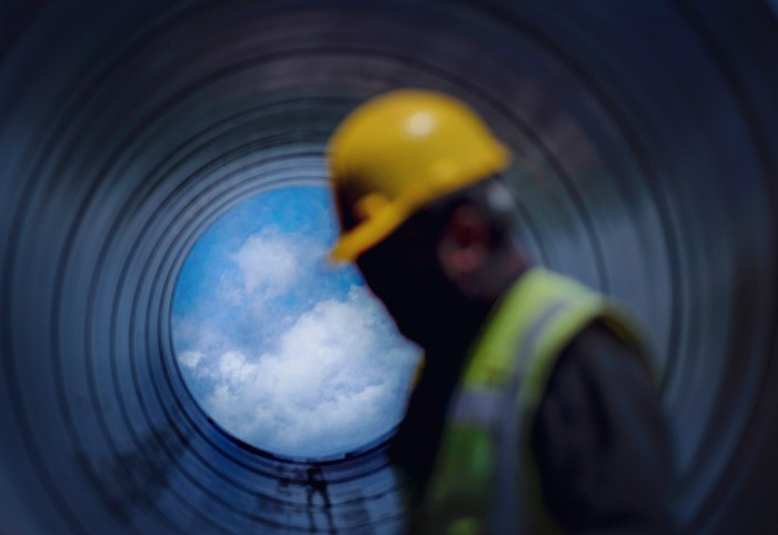 A worker walking past a pipeline with a blue sky showing through.