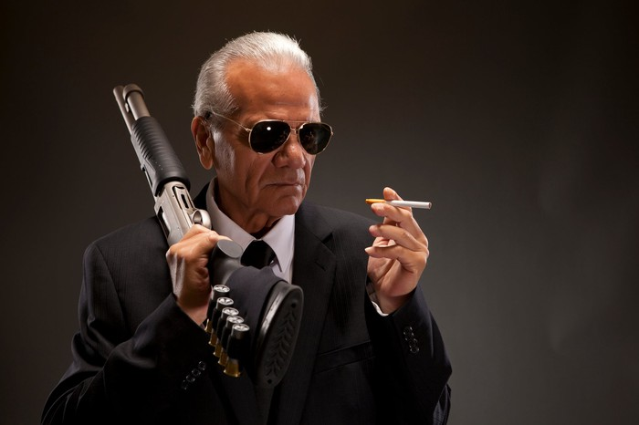Man holding a gun and smoking a cigarette.