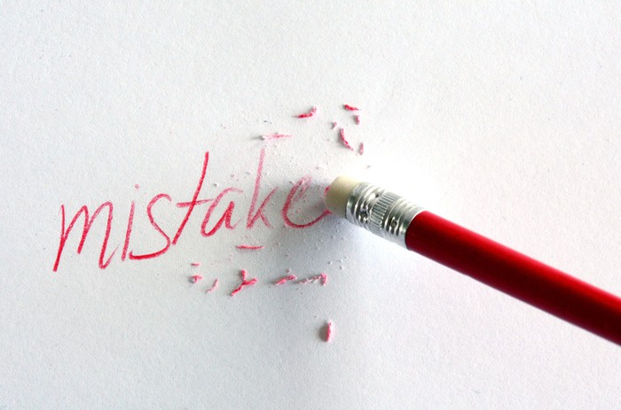 Pencil erasing the word mistake from a piece of paper.