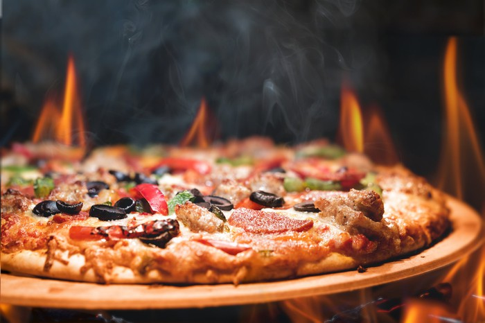 """Wood-fired """"everything"""" pizza in front of flames"""