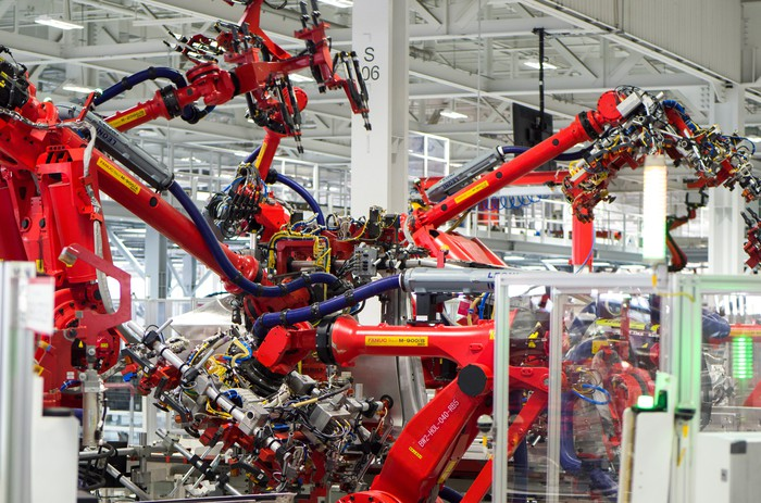 Model X central assembly point in Tesla's car factory shows robotic arms assembling the SUV.
