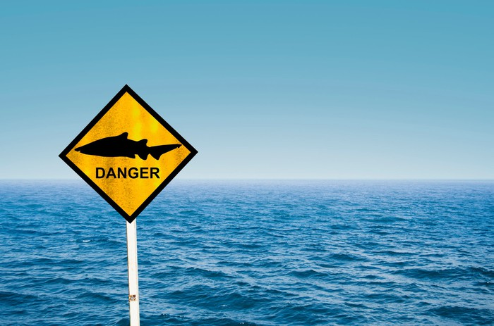 Sign with a picture of a shark and the word danger.