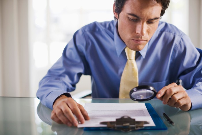 A businessman examines a financial report with a magnifying glass.