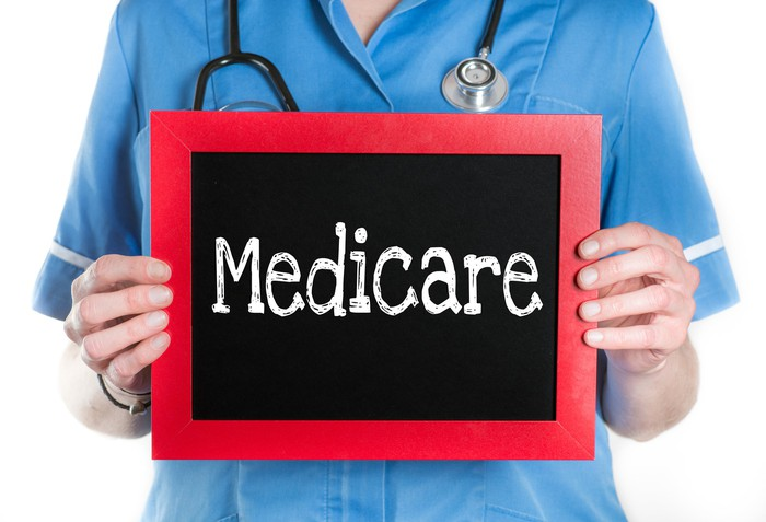 """The word """"Medicare,"""" in a frame, held by a healthcare provider."""