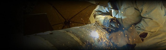 Welder working on a pipeline fitting.