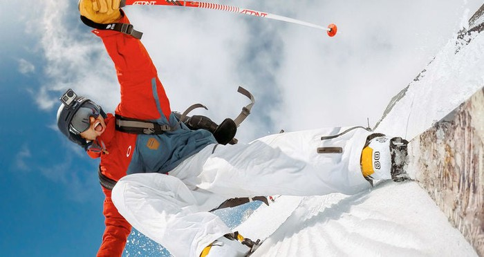 A man using a GoPro camera to record himself skiing.