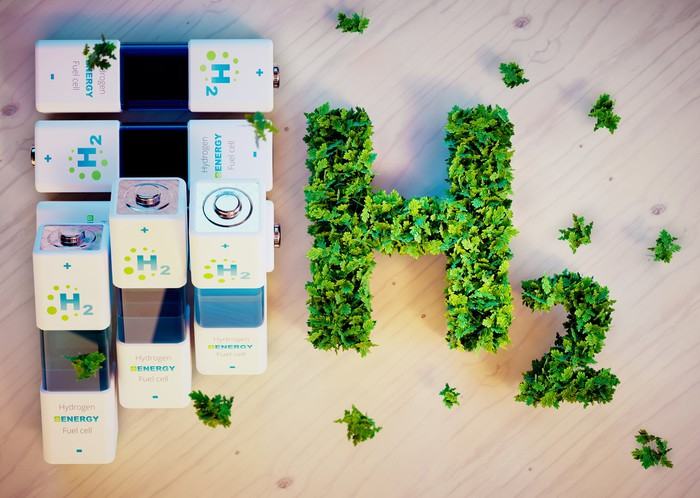 Several batteries on a table next to the symbol for hydrogen formed by green plants.