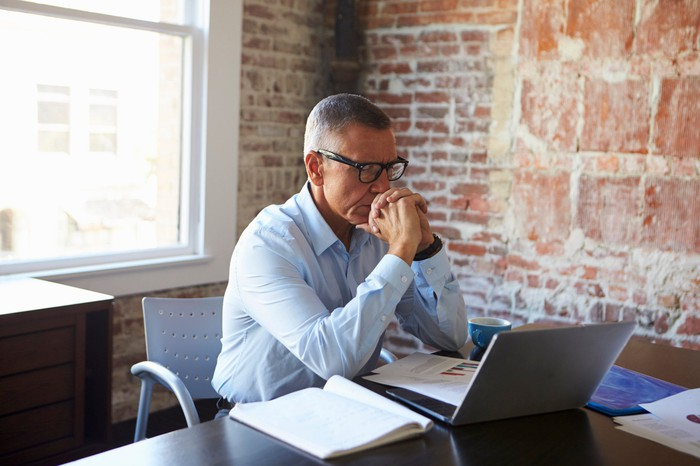 A middle-aged man looking concerned at his desk.